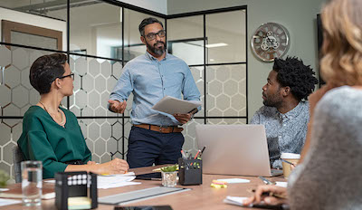 Confident mature businessman giving a presentation to his team in office. Business brief with annual goals with employees and mature boss in meeting room. Multiethnic leader training business people.